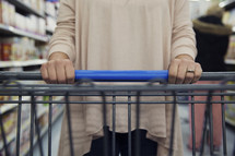 a woman pushing a shopping cart in a grocery store.