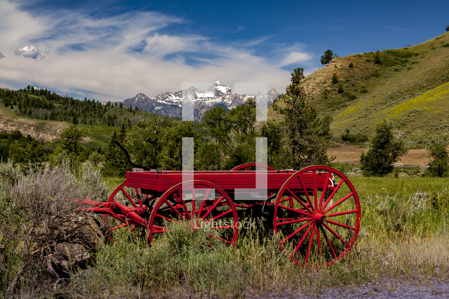 red wagon in a valley and mountain peaks