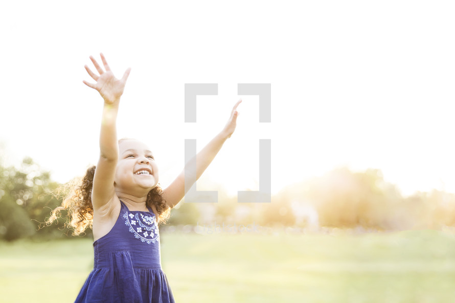 toddler standing outdoors with raised hands