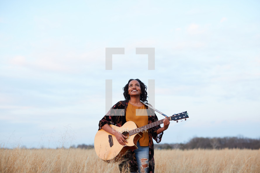 a woman standing in a field with a guitar