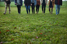 group walking in a field of grass in fall
