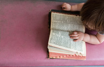 toddler reading a Bible