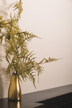 greenery in a gold vase on a mantle