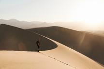 a man standing on desert sand dunes