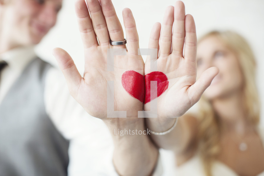 bride and groom with a red heart painted on their hands