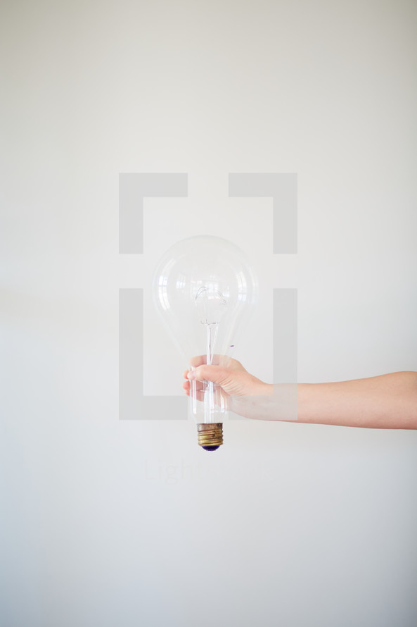 a woman holding a large lightbulb