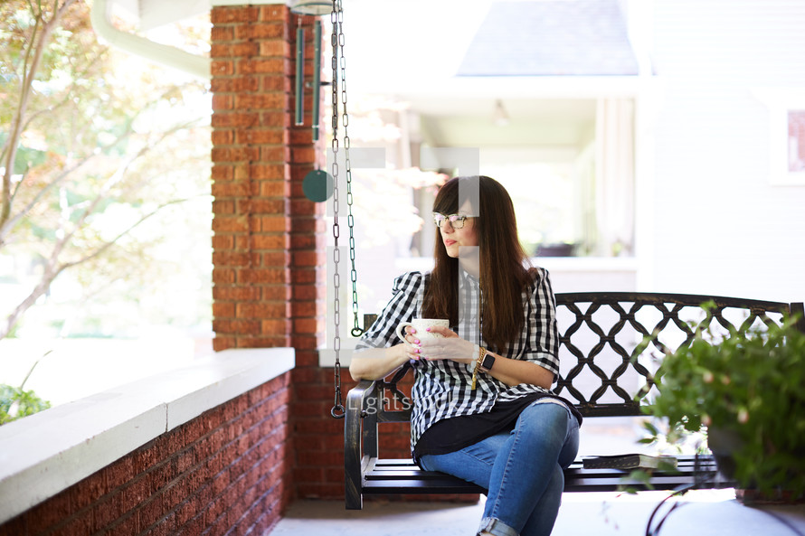a woman sitting on a porch swing with a cup of coffee