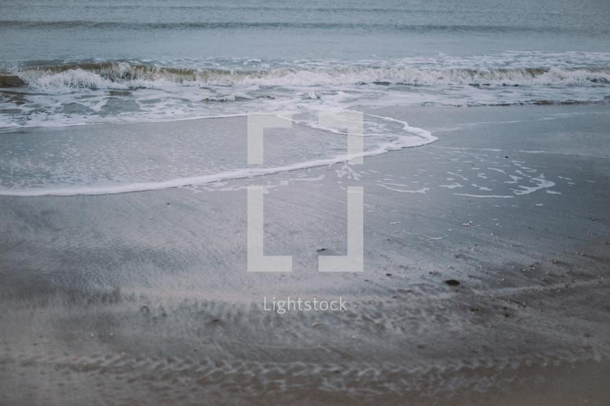 Ocean waves on a sandy beach.