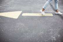 woman walking on pavement away from an arrow on the street.