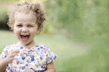 Biracial toddler girl laughing and playing outdoors.