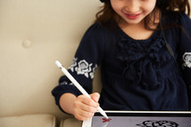 a girl drawing on an iPad