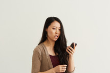 a woman looking at her cellphone and frowning