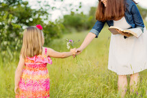 daughter picking flowers and handing them to her mother