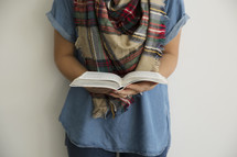 a torso of a woman holding a Bible