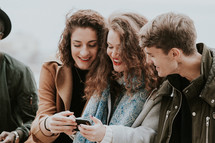friends looking at a cellphone screen