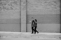 a couple walking on a sidewalk holding hands