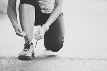 Hands tying running shoes.