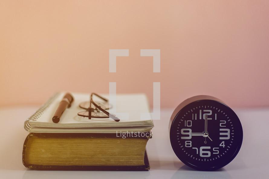 Bible, notebook, pen, and clock