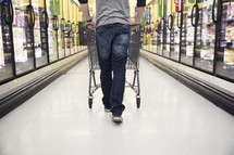 a man pushing a shopping cart through a grocery store isle.