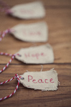 "Christmas gift tags lined up on a wood grain background, with one reading ""Peace"" in the front."
