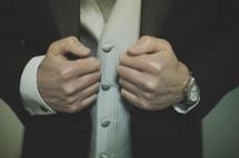 A man adjusting his tuxedo jacket