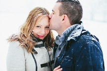 man kissing a woman on the forehead in the snow