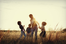 A mother and her children playing in a field at sunset.