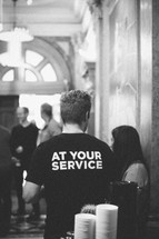 man wearing t-shirt with at your service on it