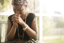 Woman sitting outside on a porch swing praying.