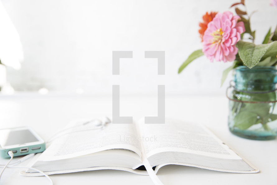 An open Bible and cell phone on a table next to a jar of flowers.
