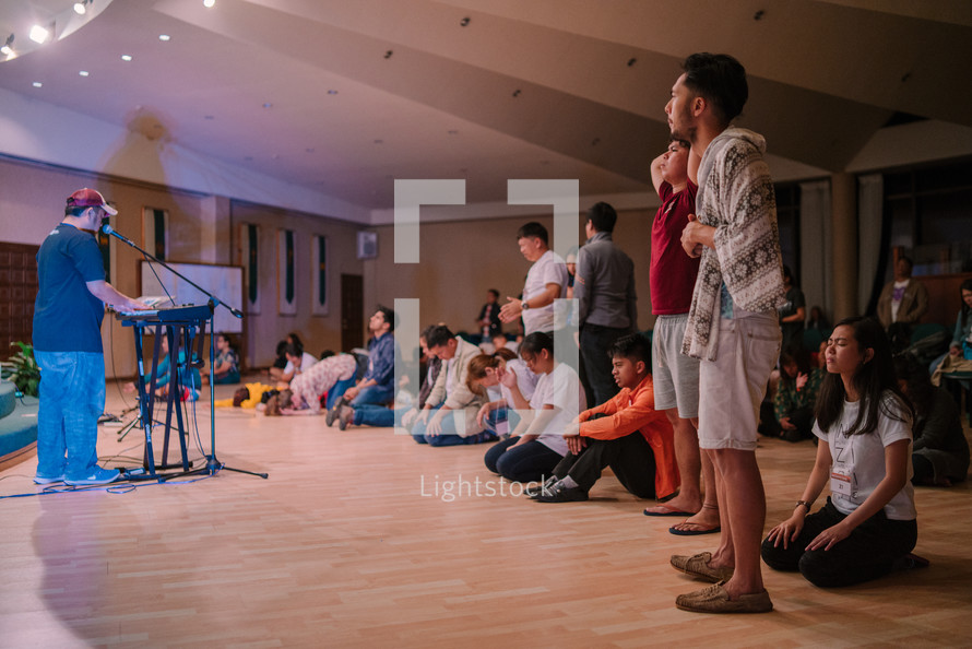 teens sitting on the floor praying during a worship service