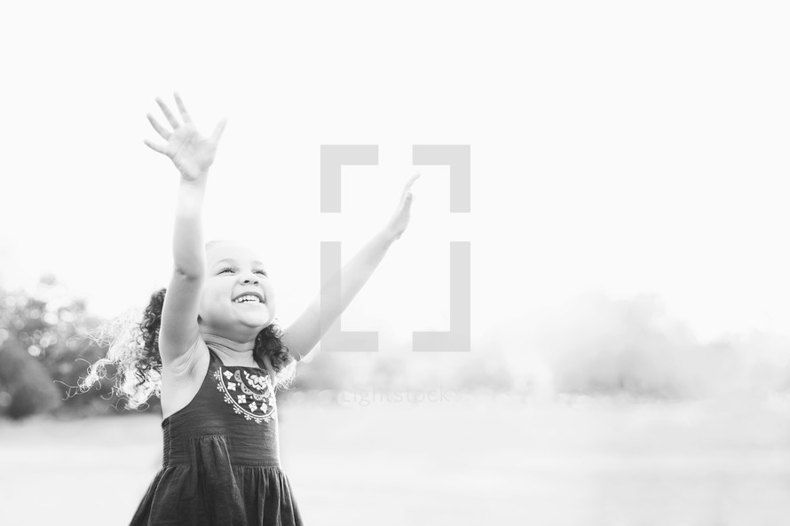 Girl standing outside with arms raised.