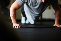 a man doing pushups in a gym.