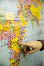 finger pointing to a map of Africa