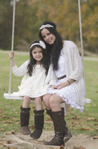 portrait of a mother and daughter on a rope swing