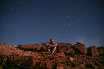 a man sitting on red rock and stars in the sky