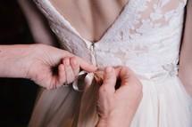 tying a bow on a brides dress