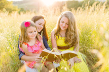 mother and daughter's reading a Bible together outdoors