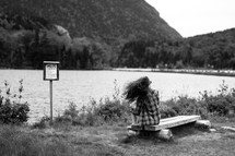 anglers sign near a river and a woman sitting on a bench