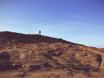 Person hiking atop a mountain.