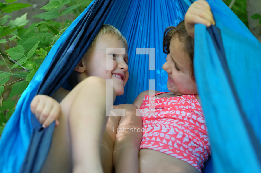 A little boy and girl playing in a blue hammock.