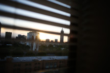 City skyline seen through window blinds.