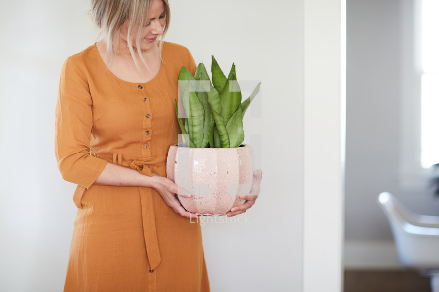 a woman holding a potted plant