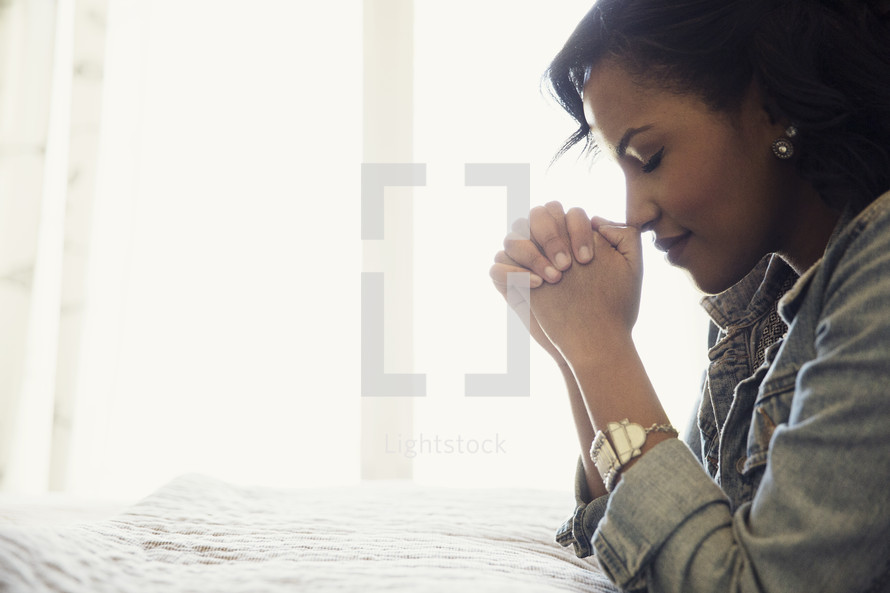 an african american woman kneeling in prayer photo by prixel