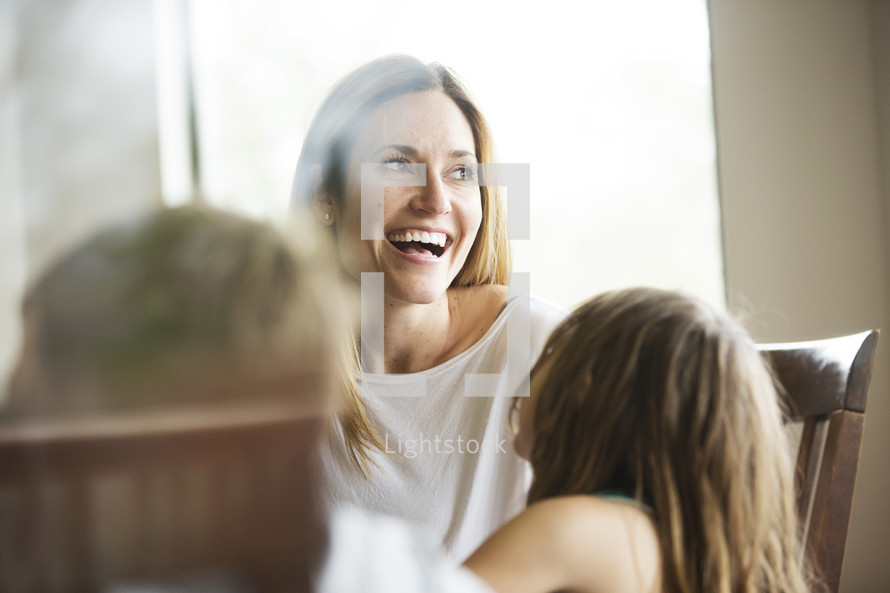 a mother laughing and talking with her kids at a kitchen table