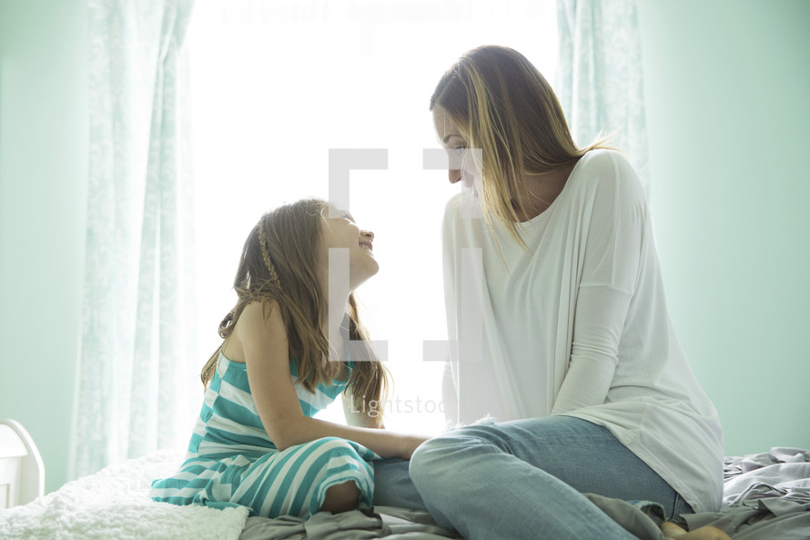 a mother and daughter in conversation in a bedroom