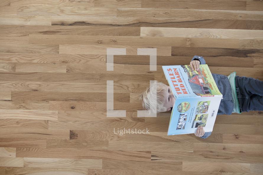 A toddler boy reading a book.
