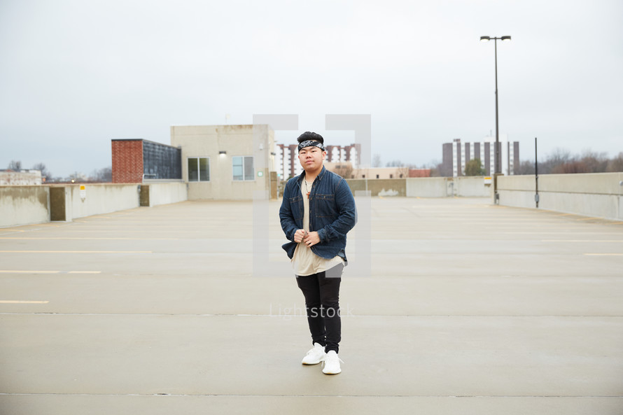 a young man standing on a parking deck