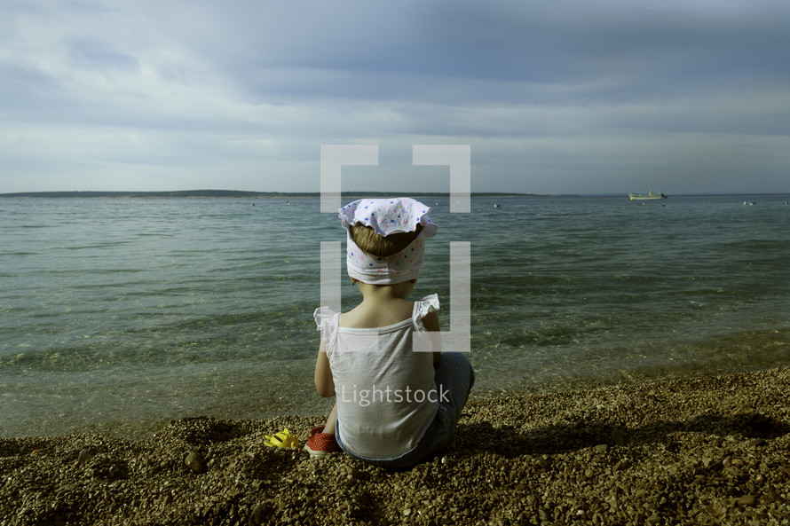 a little girl sitting on a shore