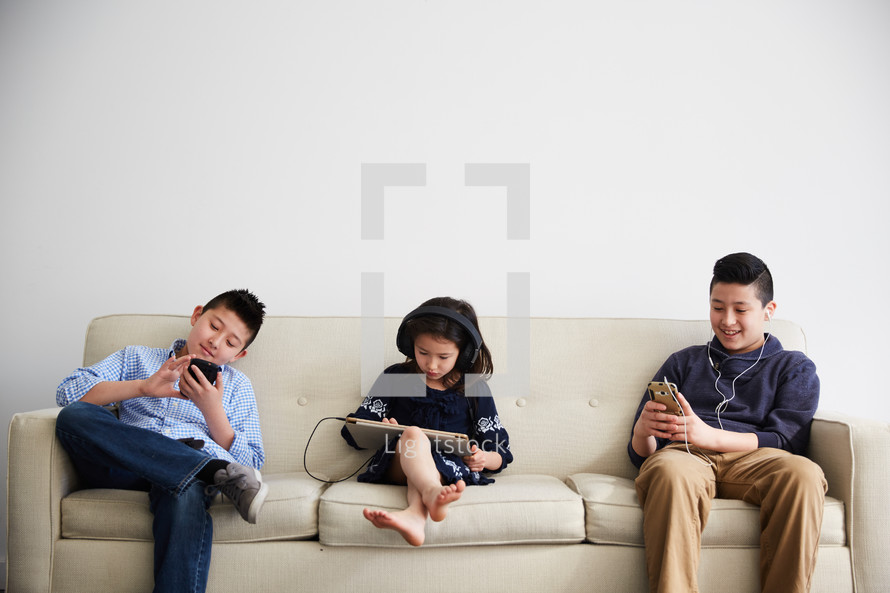 siblings using electronics on a couch